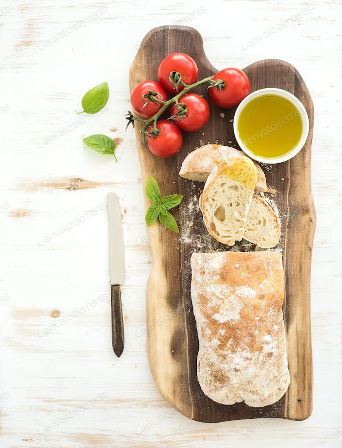 Freshly baked ciabatta bread with cherry-tomatoes, olive oil, basil and salt