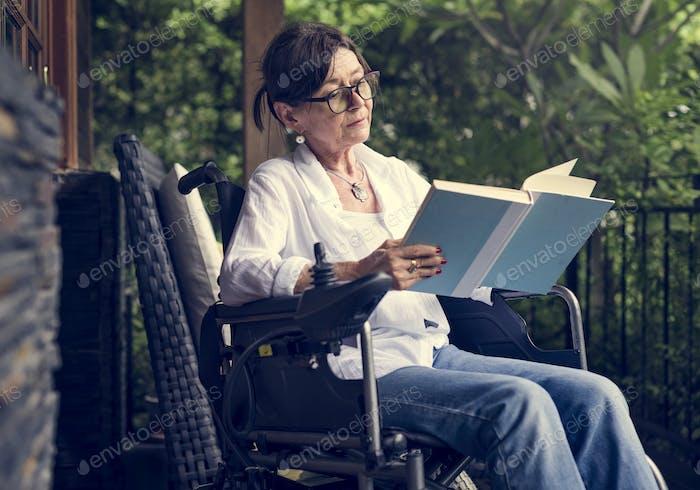 Woman reading a book in a wheelchair