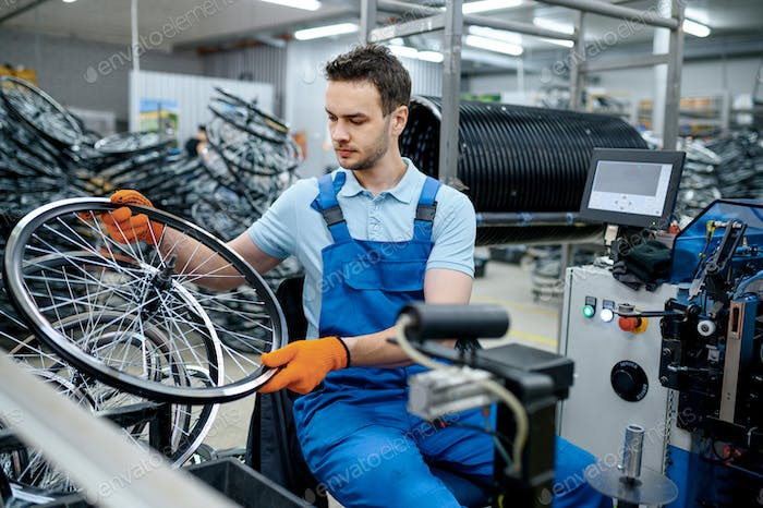 Mechanic works with bicycle wheel on factory