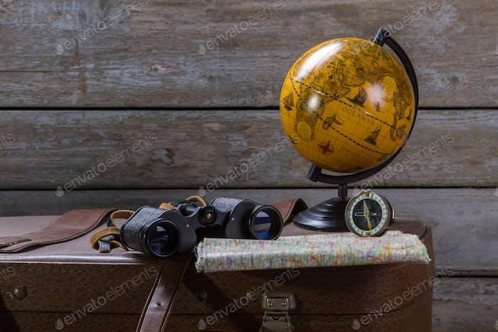 Globe with binoculars on suitcase
