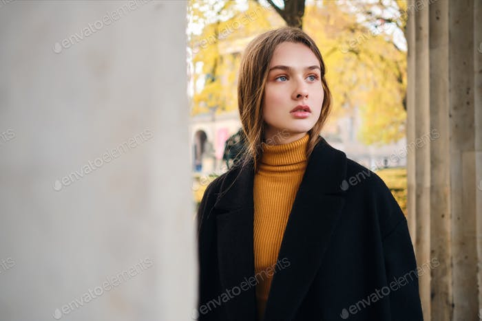 Gorgeous stylish girl dreamily looking away walking alone through autumn city street