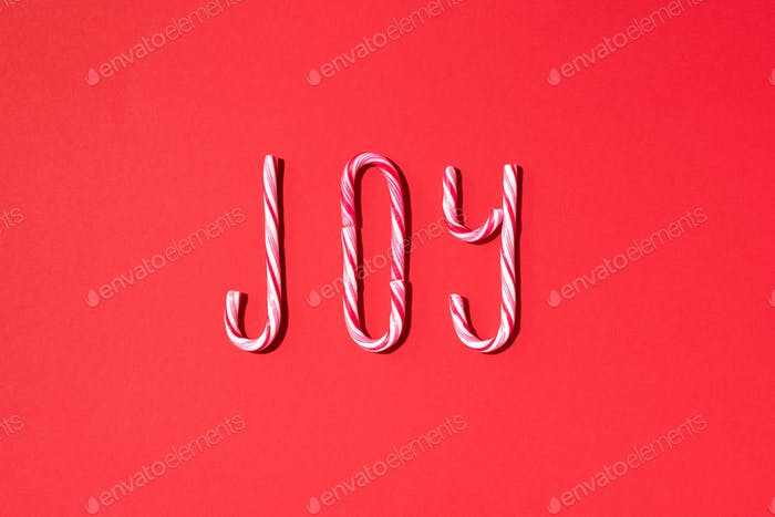 Joy word written with Christmas candy canes on red background. Top view. Flat lay. New year and