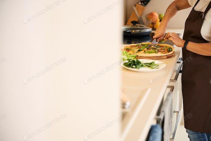 Dividing fresh homemade pizza into separate pieces