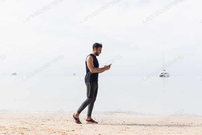 Full Length Shot Of Male Runner Using Cell Smart Phone On Beach While Jogging On Seaside Man Young