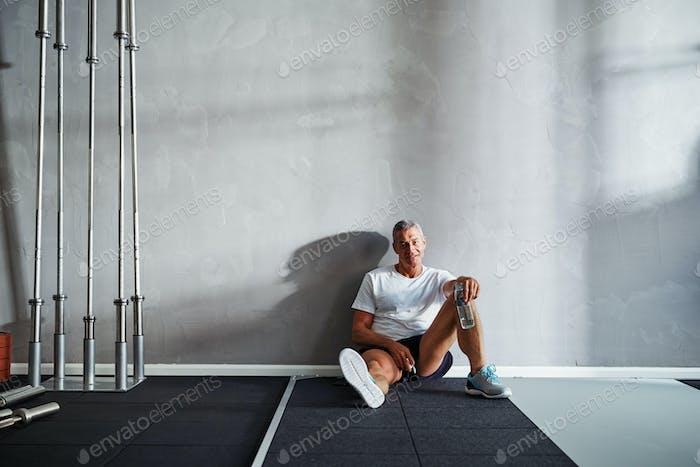Lächelnd reifen Mann ruhen nach dem Training aus in der Turnhalle