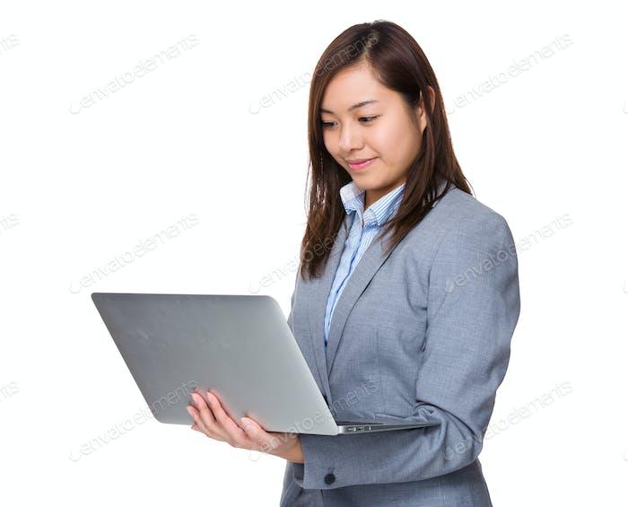 Uso joven de la mujer de negocios de la computadora portátil