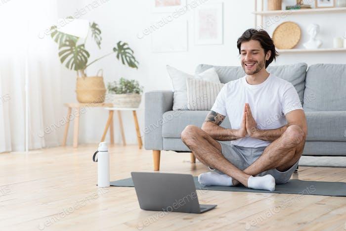 Lächelnder junger Mann sitzt in Lotus Pose