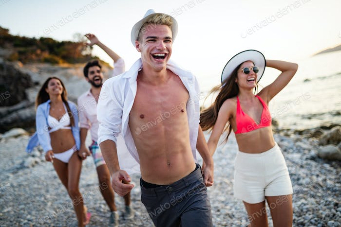 Group of excited young friends having fun together at he beach