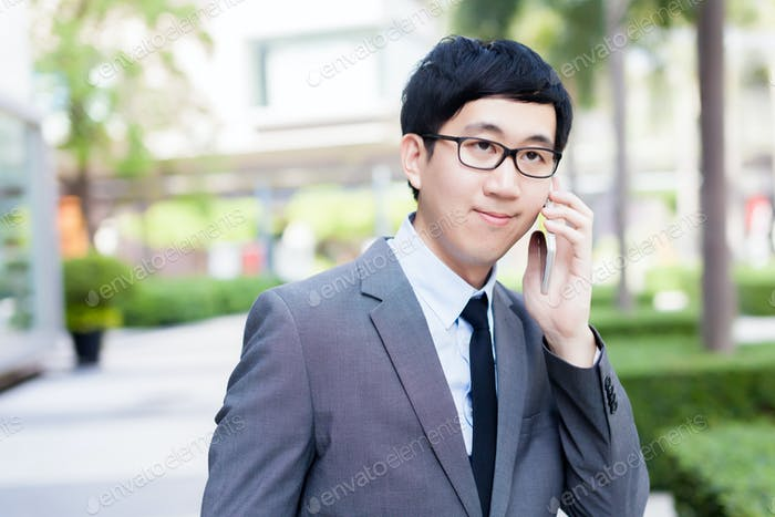 Young Asian businessman in elegant suit talking on the phone with the grin on his face