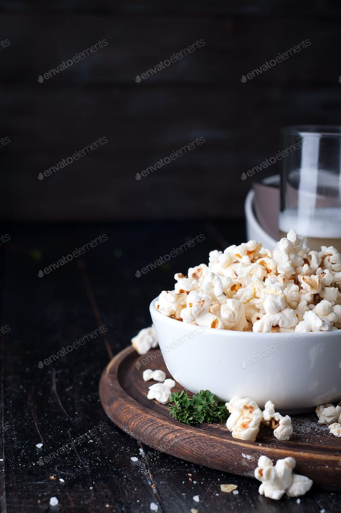 Popcorn in  bowl over wooden background