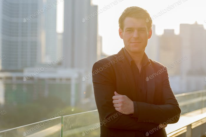 Young handsome businessman with arms crossed against view of the city