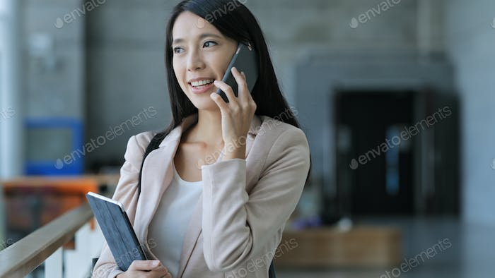 Business woman talk to cellphone and holding tablet computer