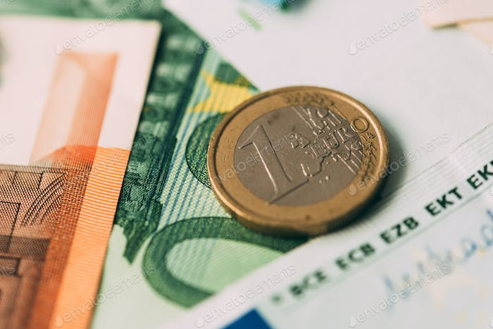 Euro coins on cash stack closeup