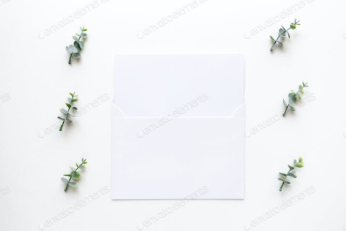 Wedding invitation card and oregano branches on white marble. To