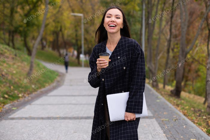 Young attractive cheerful woman in coat with coffee to go and laptop joyfully walking in autumn park