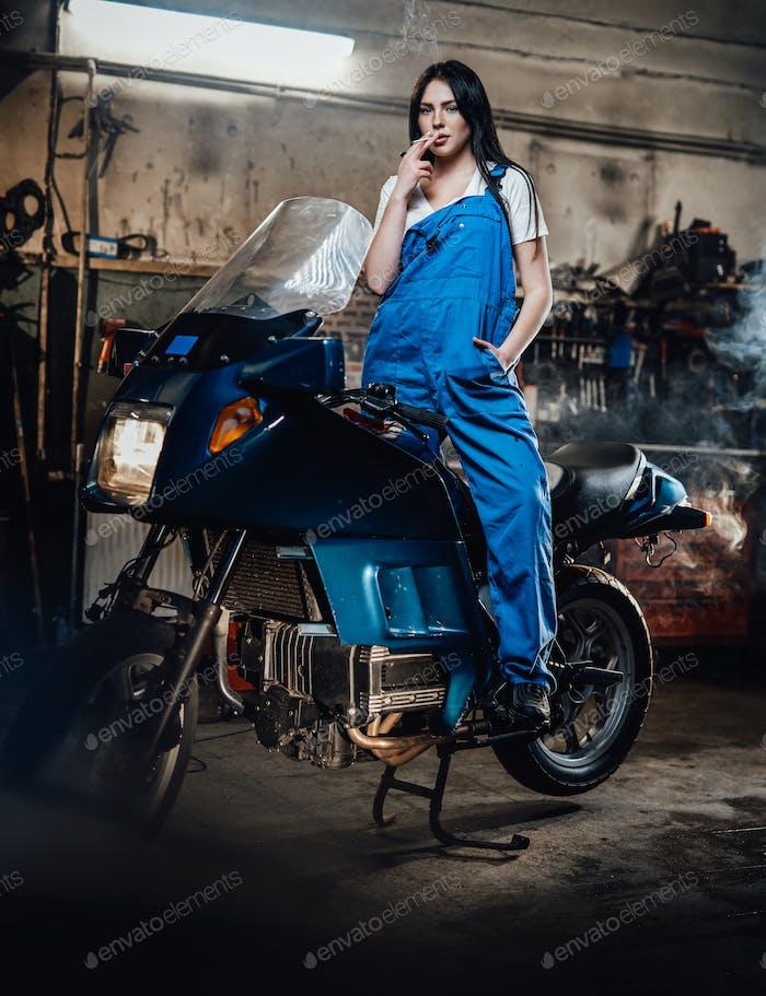 Женщина-механик расслабляющий курить сигарету, стоя на спортивном велосипеде в гараже или мастерской