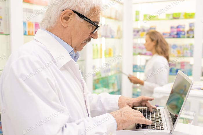 Senior male pharmacist searching for medicine in computer base by workplace