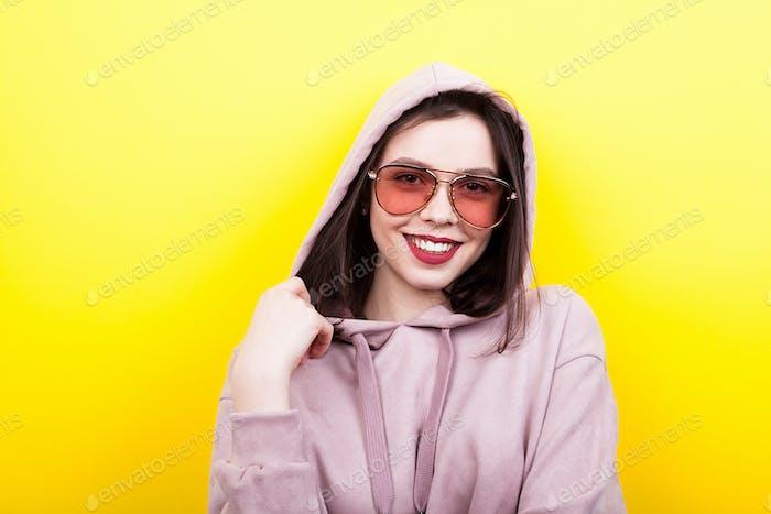 Lächelnd coole Frau trägt eine Kapuze und Brille