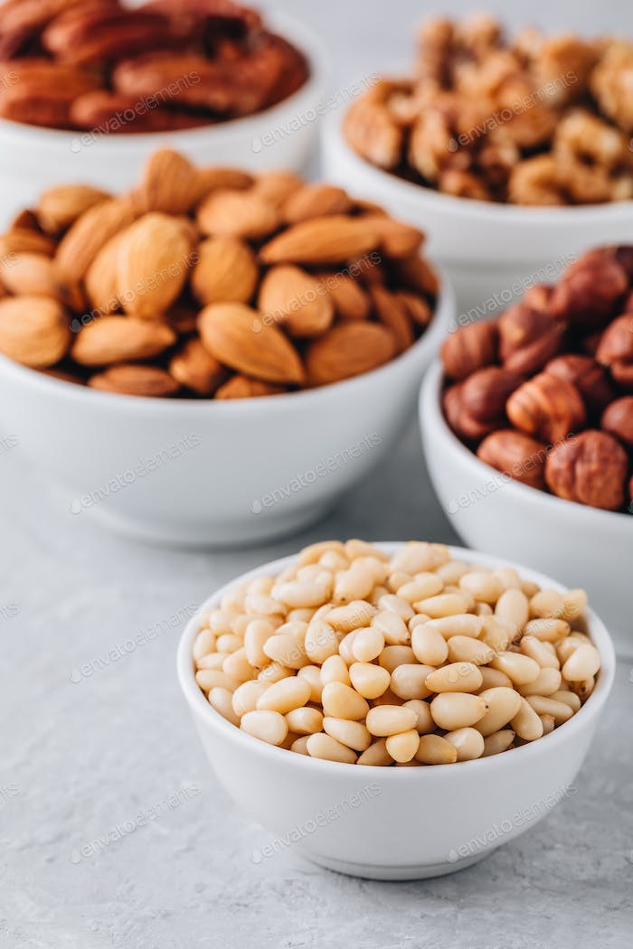Pine nuts, almonds, pecans, walnuts and hazelnuts in white bowls on grey background. Mixed nuts.