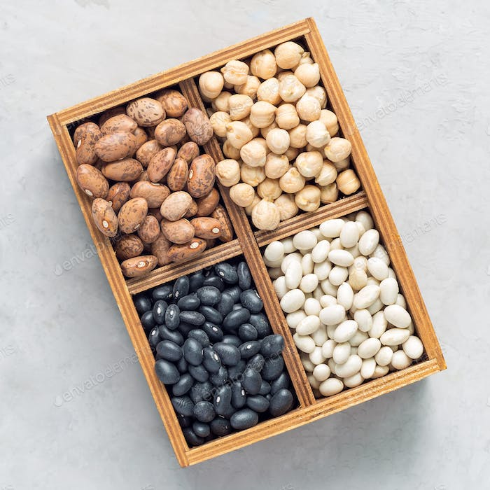 Different kinds of beans in a wooden box on concrete background, square format