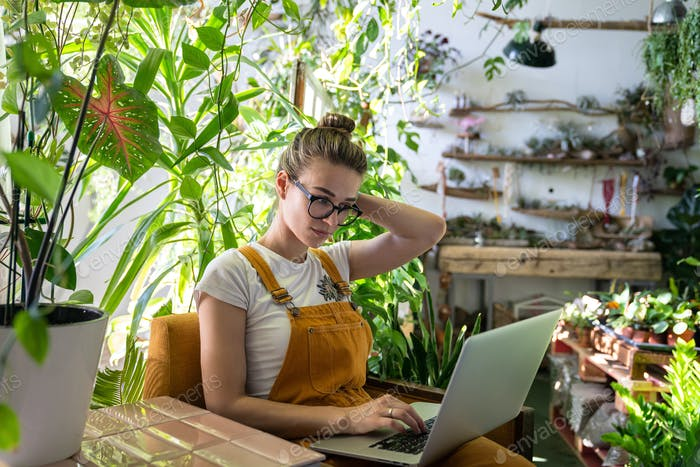 Woman florist sitting on chair in greenhouse working on laptop. Home gardening, freelance.