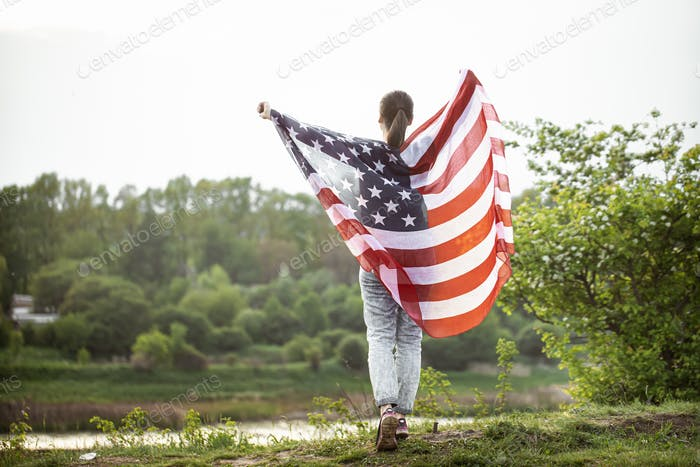 A young woman in nature with an American flag.
