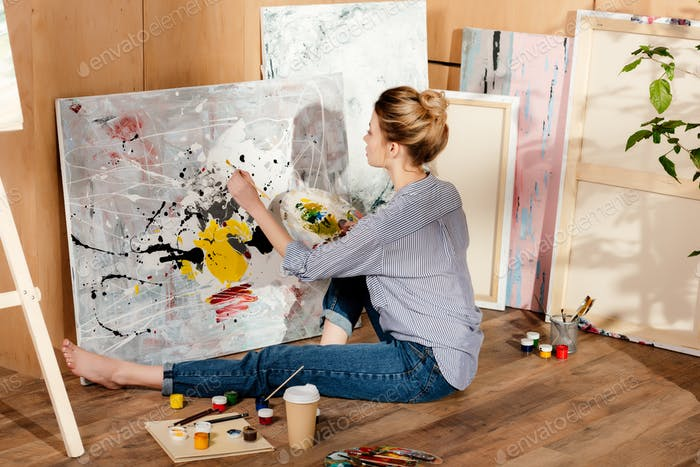 красивая молодая художница сидит на полу и рисует картину в художественной студии