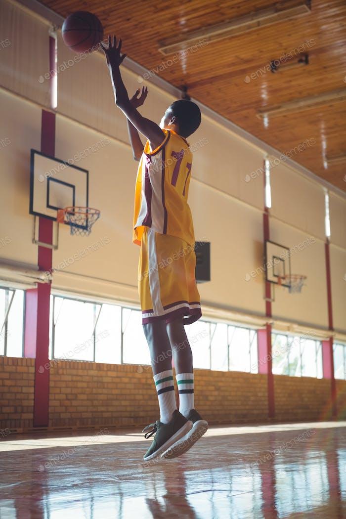 Full length of teenage boy playing basketball