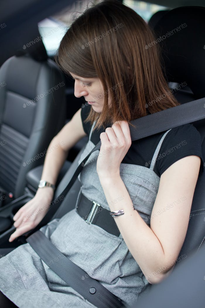 Road safety concept - Pretty young woman fastening her seat belt
