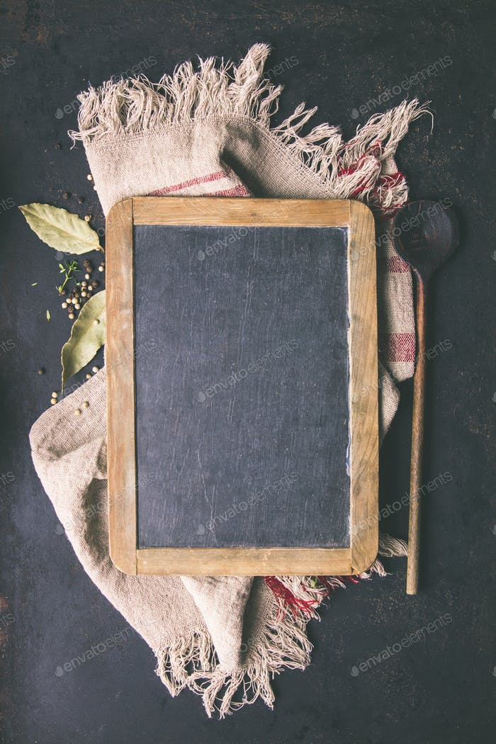 Black board, wooden spoon and spices - cooking background