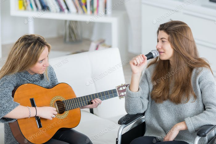 Girl in wheelchair singing along to friend playing guitar