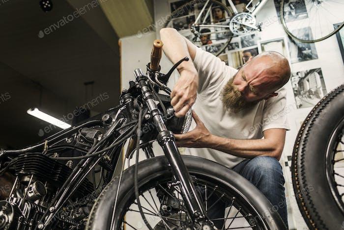 Man repairing retro motorcycle in workshop