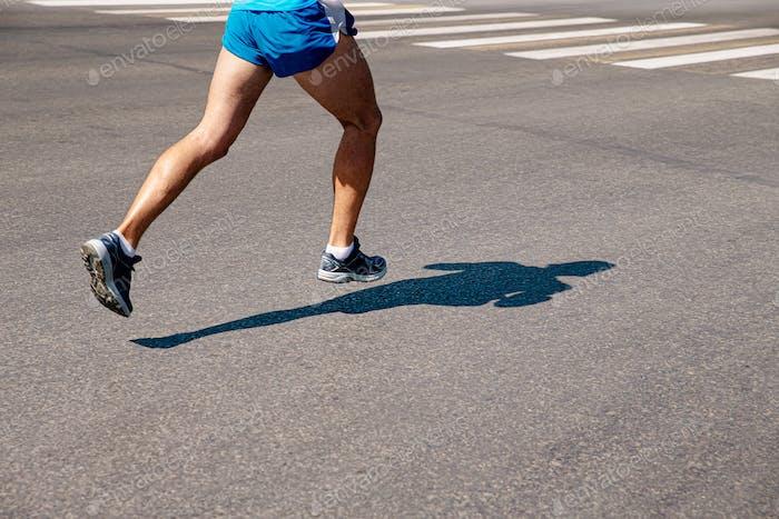 Beine männlicher Läufer laufen auf grauem Asphalt