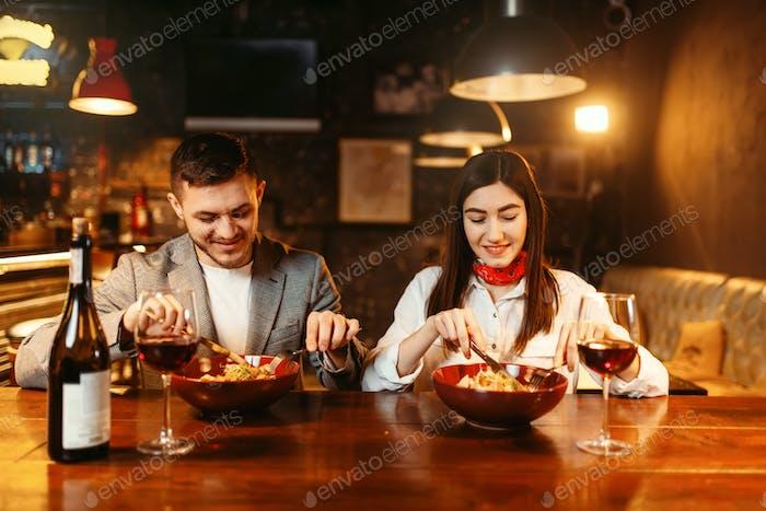 Love couple flirting at wooden bar counter