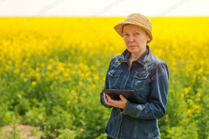 Female farmer using tablet computer in rapeseed field