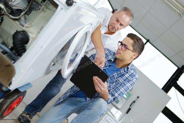 Men inspecting washing machine