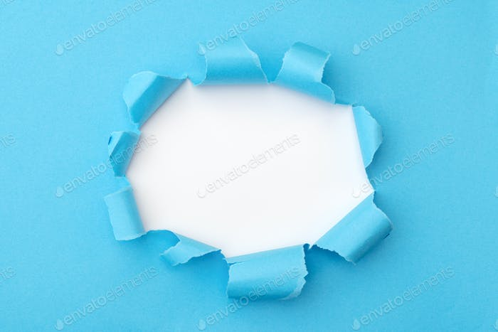 Blue paper with ripped hole in the middle background