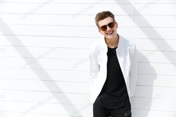 Cheerful man in sunglasses standing over white wall background
