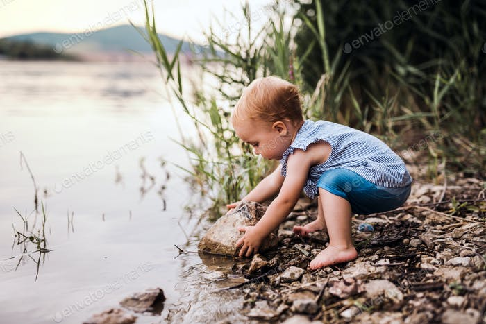 A small toddler girl playing outdoors by the river in summer.