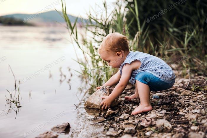 Una niña pequeña jugando al aire libre junto al río en verano.