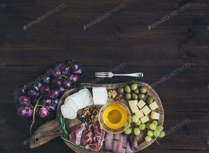 Wine appetizers set: meat and cheese selection, honey, grapes