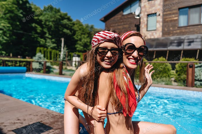 Mother and daughter in swimsuits at border of pool