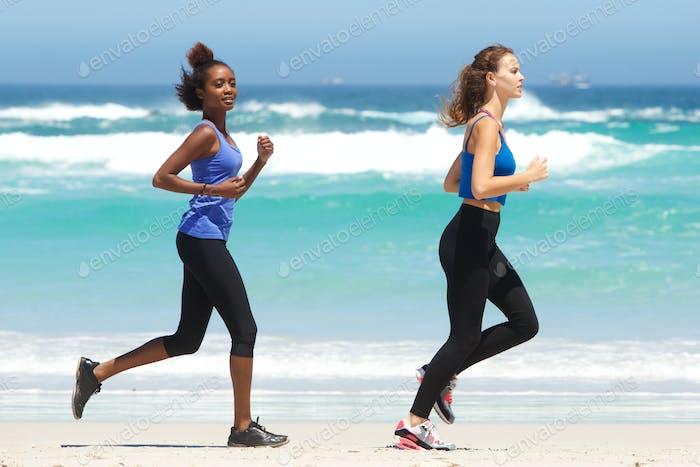 Vertical de Duración completa de dos Mujeres jóvenes en forma corriendo en la Playa