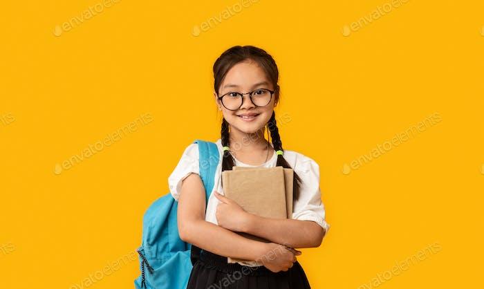 Cheerful Japanese School Girl Hugging Book Standing Over Yellow Background