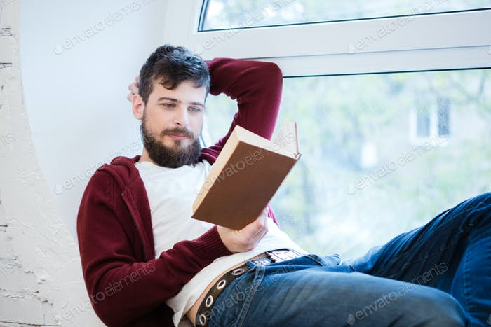 Relaxed young guy lying on window sill and reading