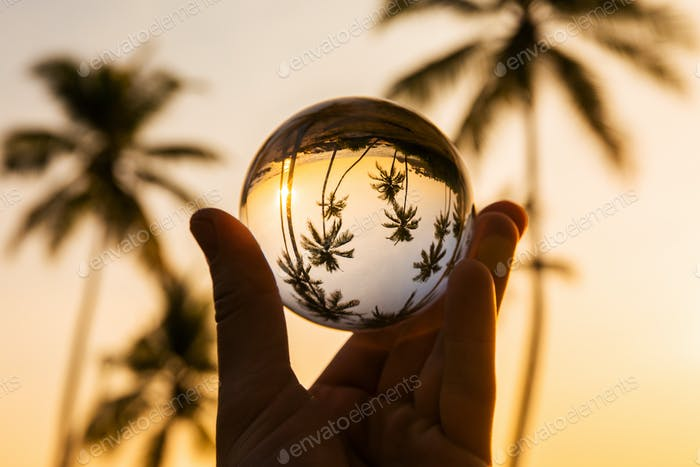Reflection of tropical beach at sunset in a glass ball
