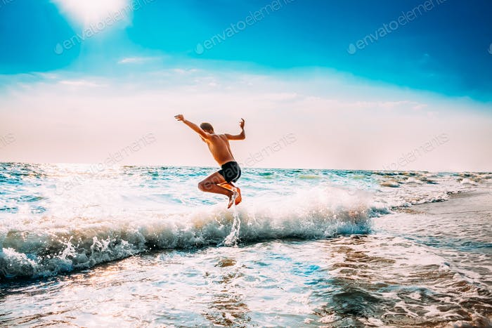 Boy Having Fun And Jumping In Sea Ocean Waves. Jump Accompanied