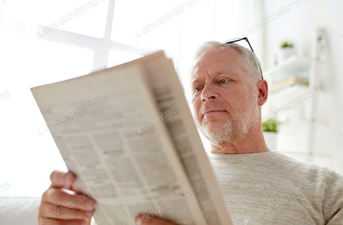 close up of senior man reading newspaper at home