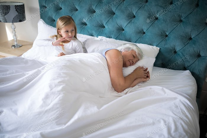 Grandmother sleeping on bed while girl sitting behind her
