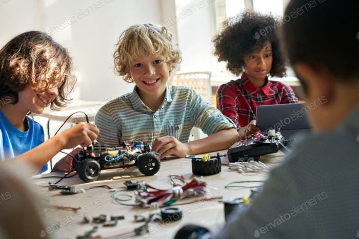 Happy schoolboy with group of classmates on science lab work at school.